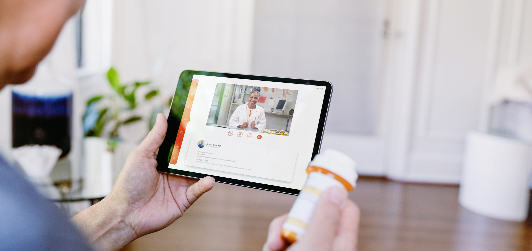 While holding a prescription medication container, an unrecognizable senior man video chats with a female doctor. The man is asking questions about his medication.